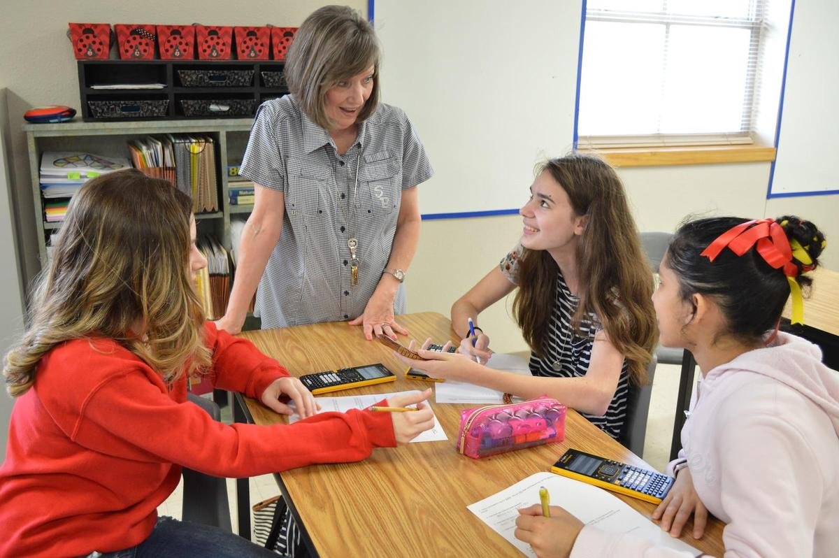 teacher working with students on math