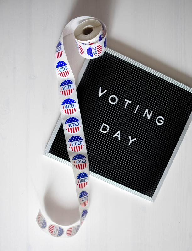 Photograph of voting stickers and announcement board that says