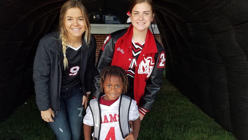 Kindergarten Student with high school cheerleaders