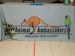 Animal Ambassadors logo on a tablecloth.