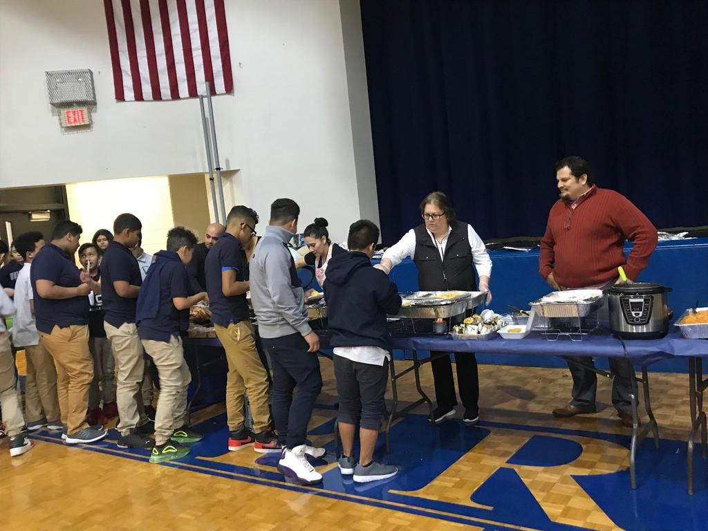 students lined up and getting food from the head table while mr. hurtado looks on