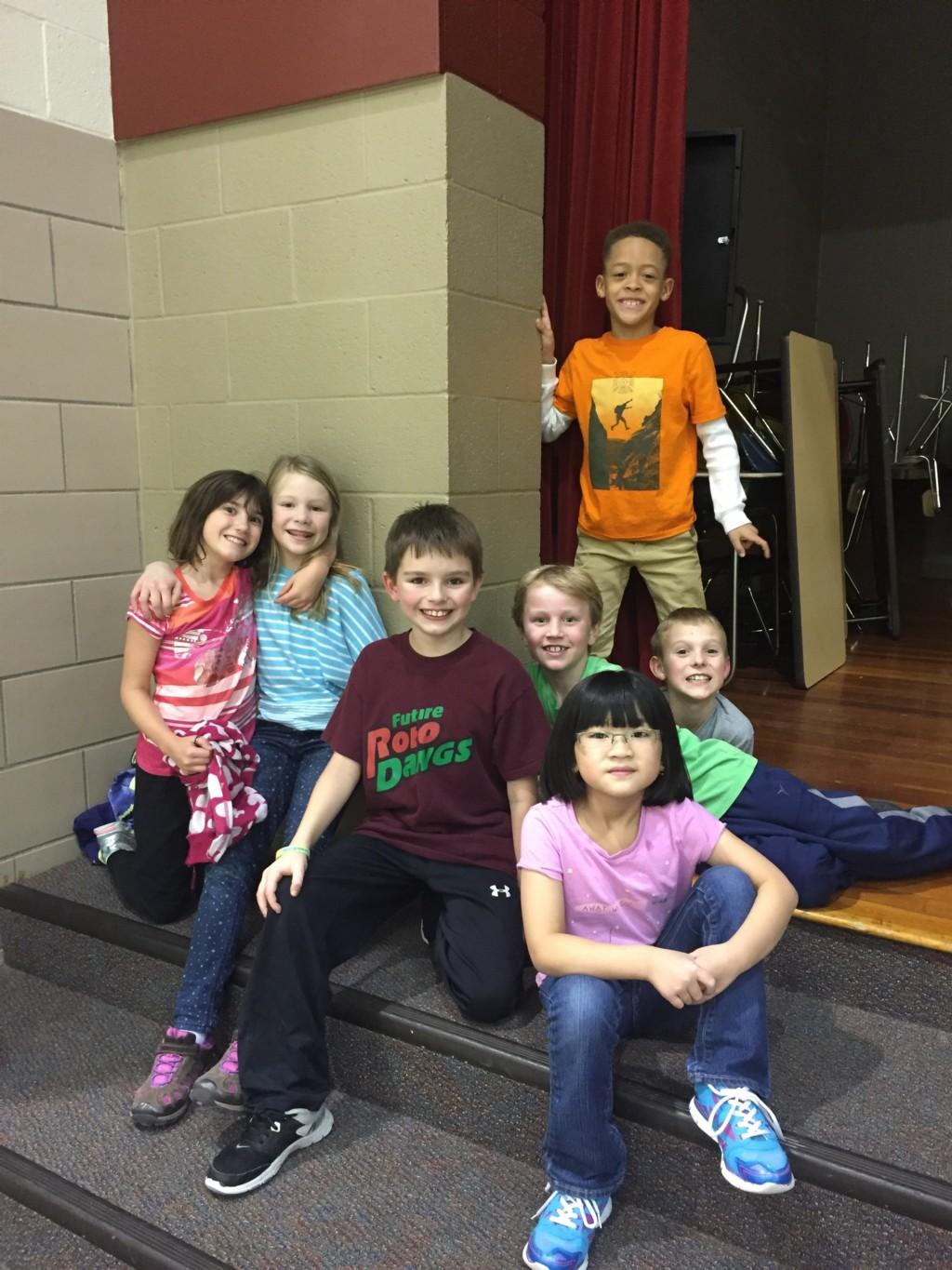 students pose for camera on steps to stage in gym