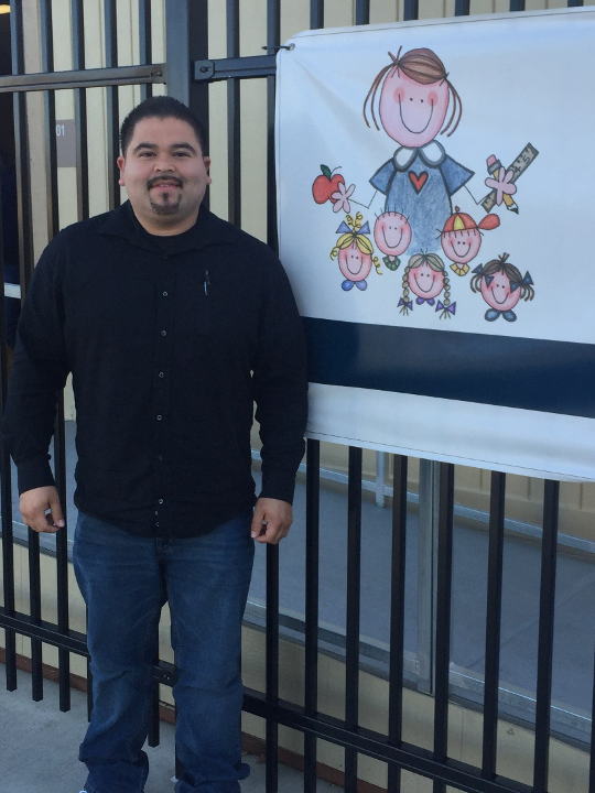 Ruben Grajeda in front of a Preschool sign.