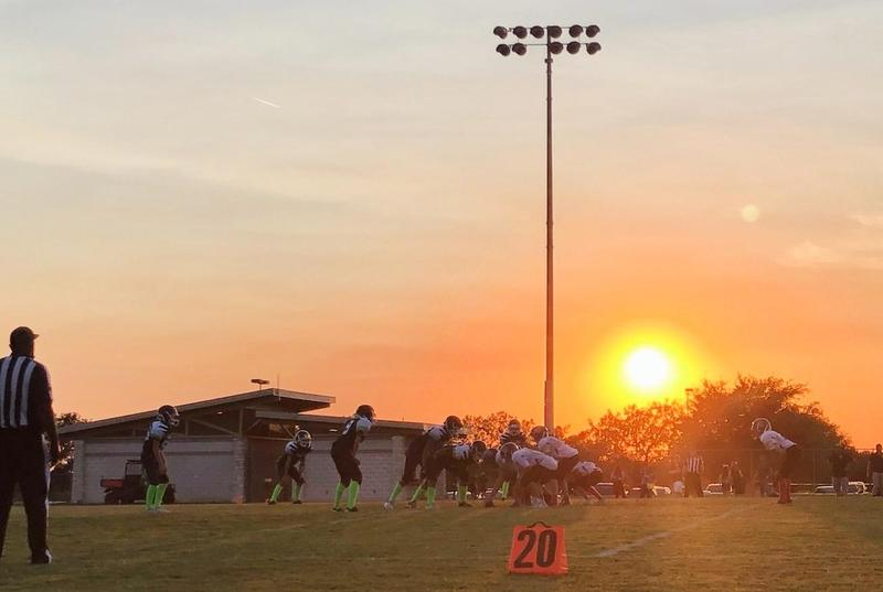 NYOS football players playing a game at sunset