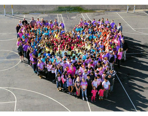 Aerial drone shot of 100s of kids in multicolored t-shirts forming a large heart on outdoor blacktop athletic courts.