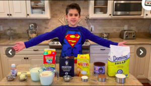 boy showing off the ingredients needed for the chocolate cupcakes