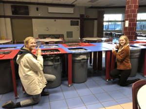 two girls bend down by recycling table in cafeteria