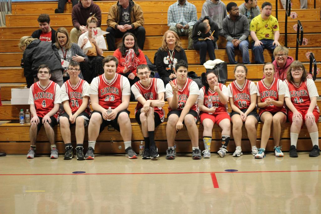 Co-ed basketball team sitting on a bench and wearing red uniforms.