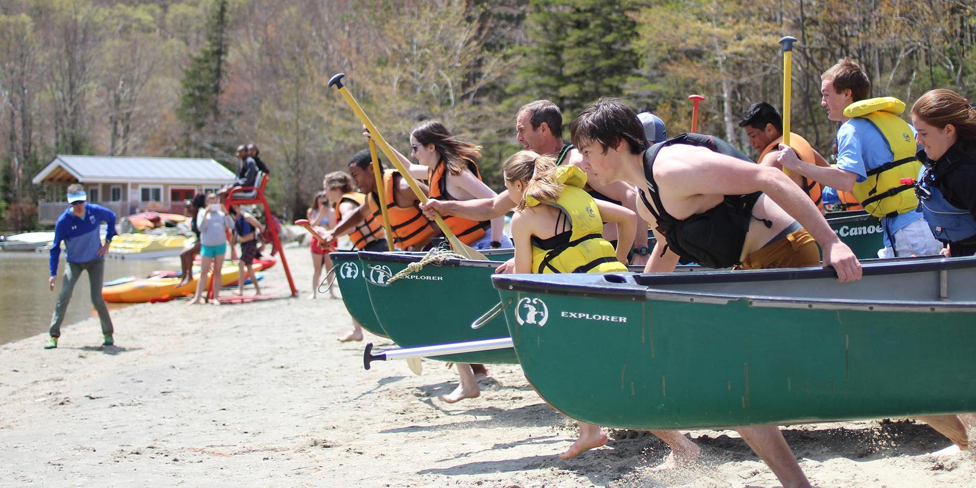 Students and adults racing into the water for a canoe race on Beach Day.
