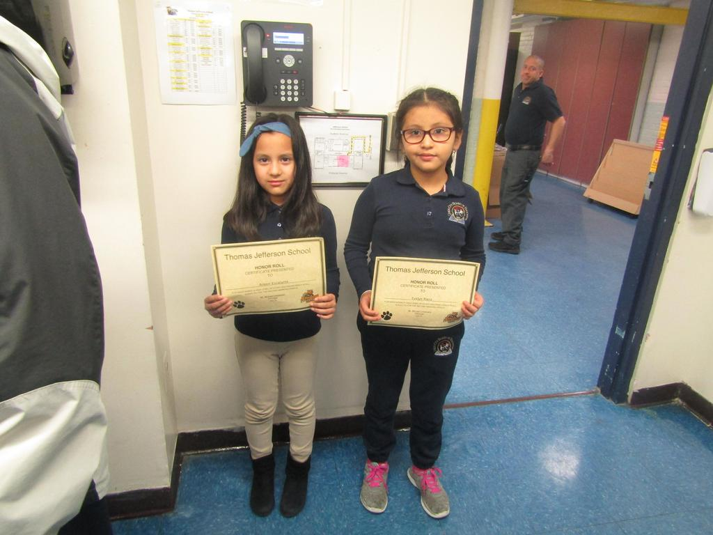 two girls showing off their certificates