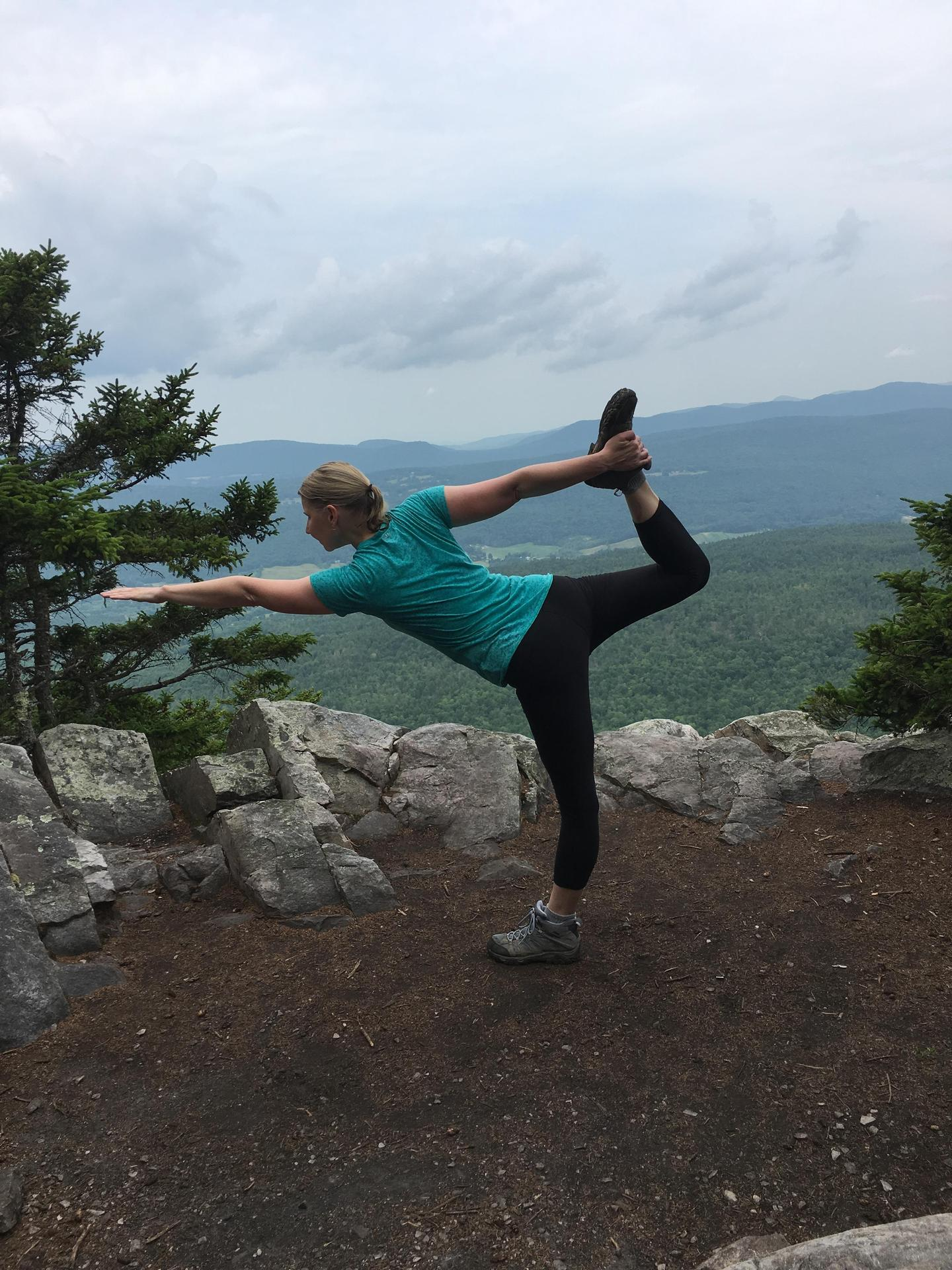 Yoga pose, standing bow, on the hiking trail