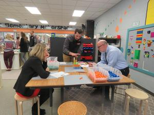 East Grand Rapids administrators watch a demonstration of how Lee Elementary teachers use Legos in the Makerspace room to teach math lessons.
