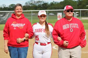 A photo of a senior softball player and her parents.