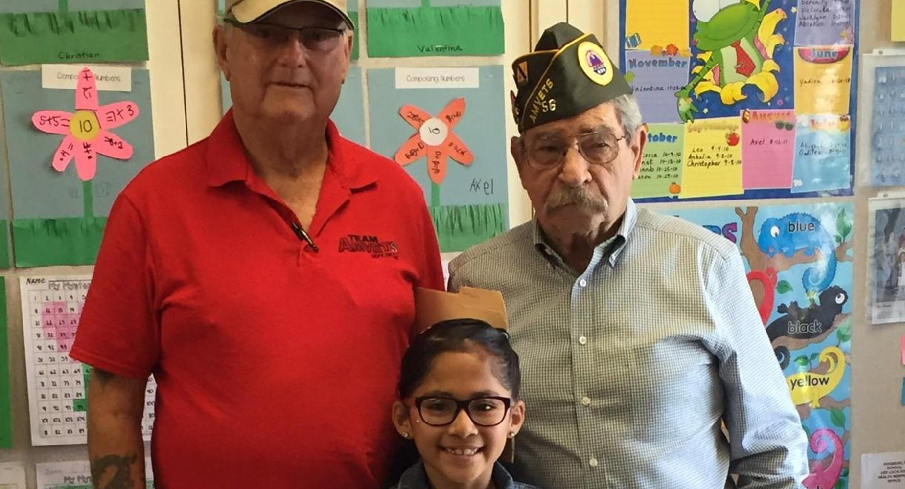 Roosevelt Student posing with two veterans.