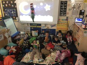children wearing pj's laying on the class rug with stuffed animals, pillows, blankets and reading