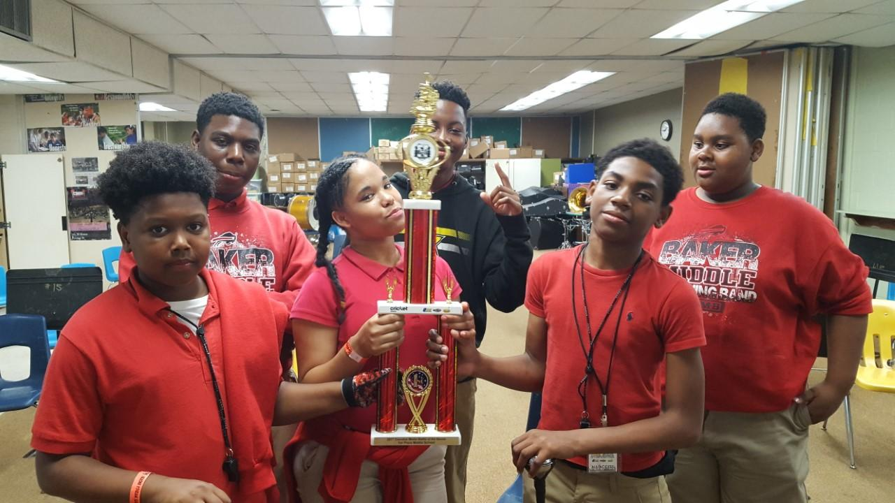 Six Baker Middle Band Students hold winning trophy from battle of the bands