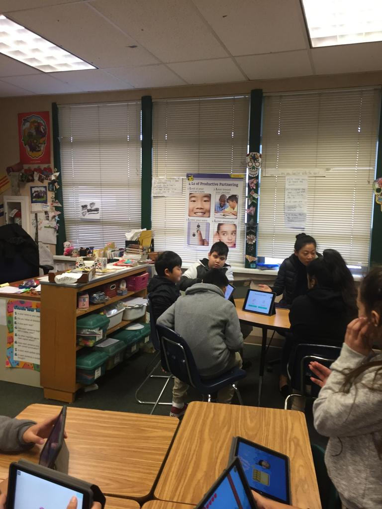 students scattered throughout classroom coding on iPads