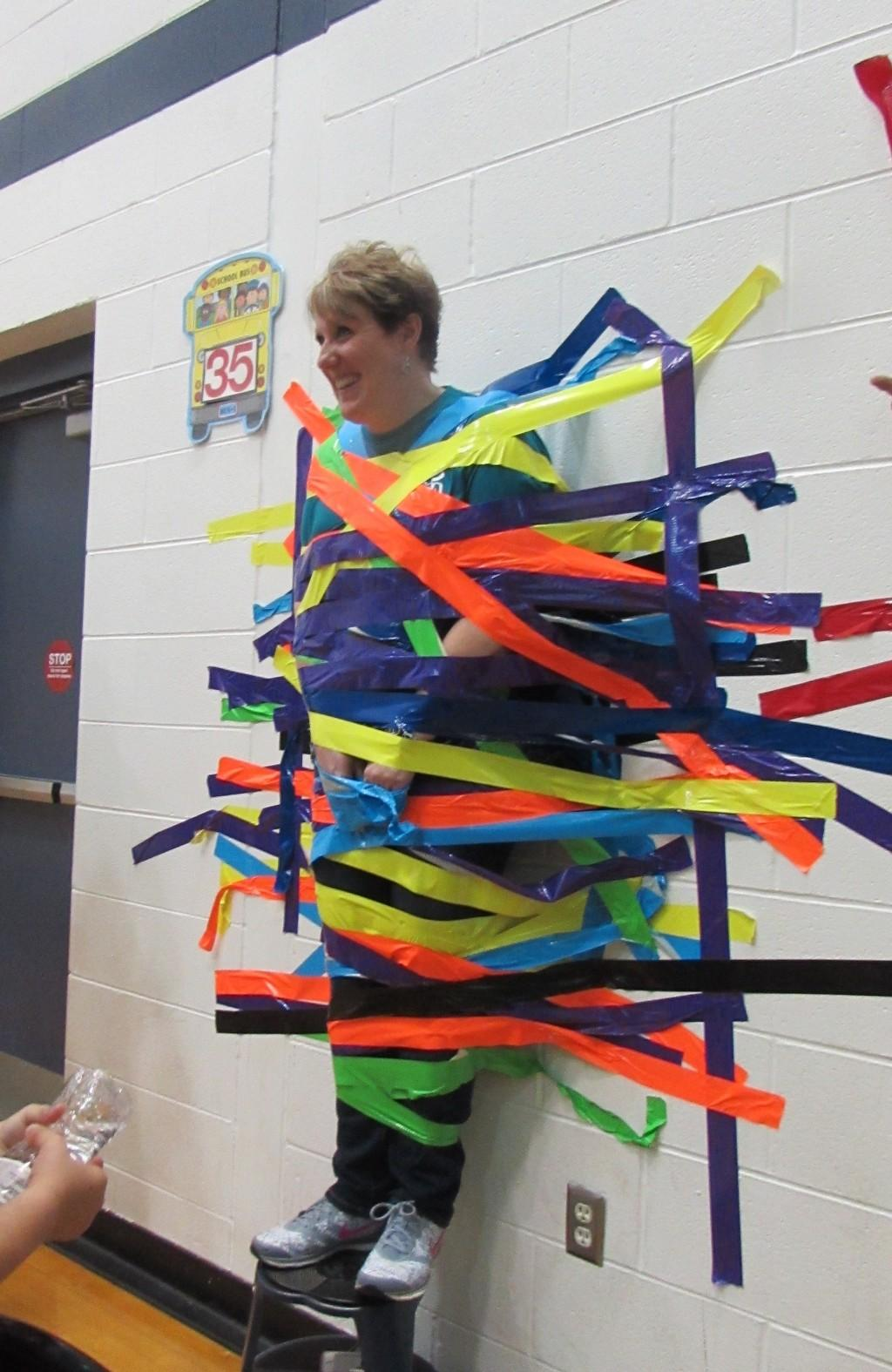 Mrs. Harrison is taped to a wall!
