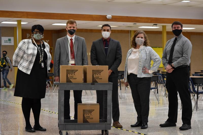 Management Training for Cintas Corporation's Justin Pines (middle) joins Prince George High School Assistant Principal Donna Branch-Harris (left), Principal Mike Nelson (second from left), and Assistant Principals Christina Pope (second from right), and Matt McAllister (right) as the company donated 12 gallons of hand sanitizer for the school. (Prince George County Public Schools photo)