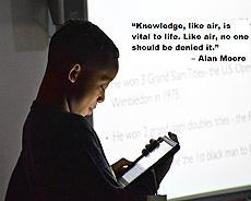 "Student at a whiteboard doing a presentation from his ipad. Text:""Knowledge, like air, is vital to life. Like air, no one should be denied it."" – Alan Moore"