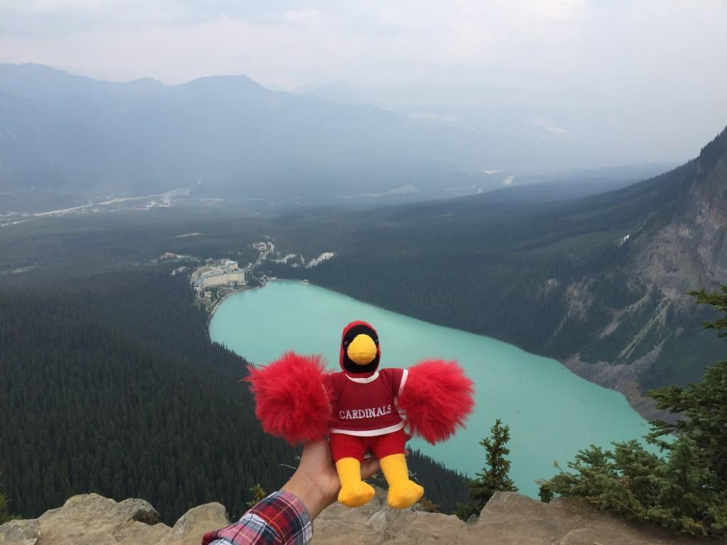 My friend holding a Cardinal plush a nice view of a turquoise lake on Banff's beehive trail