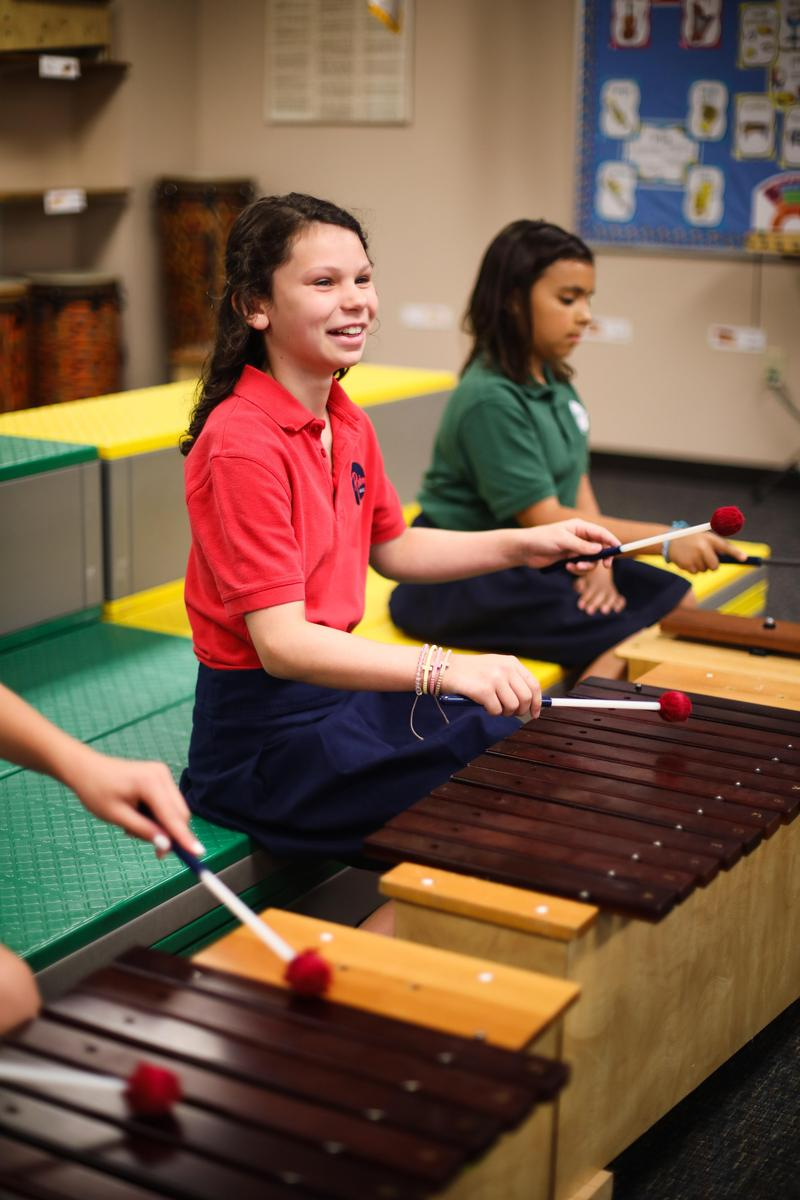 girl student playing xylophone in music class