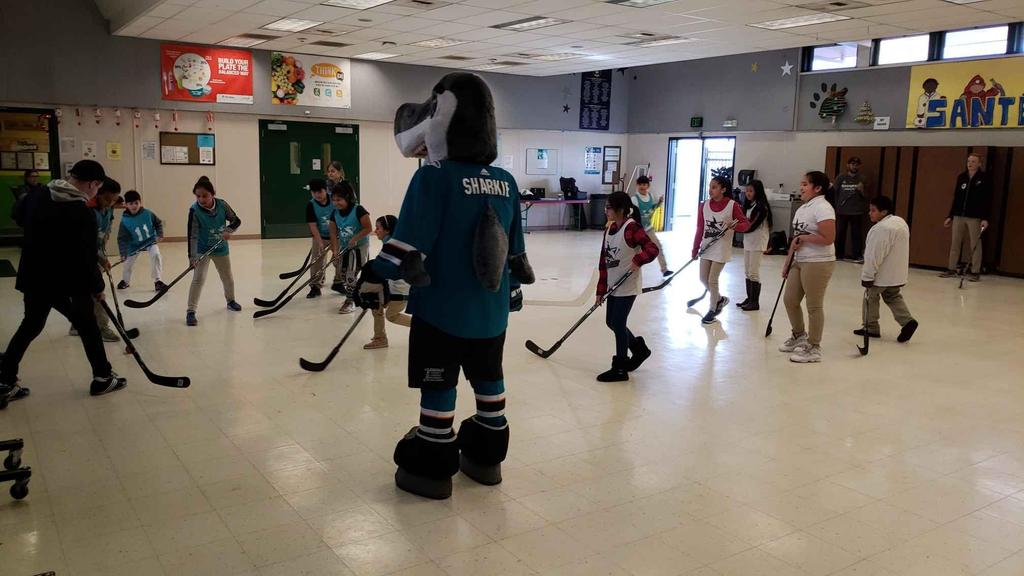 students use hockey sticks in cafeteria with sharkey the sharks mascot
