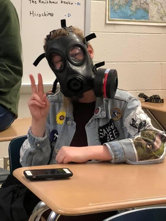 a student dressed in a gas mask.