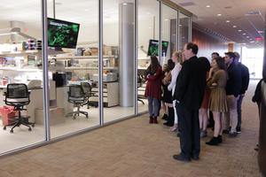 Dr. Williams and students stand outside a lab. The glass windows allow them to see inside.
