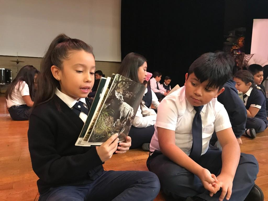 students reading on stage