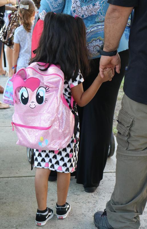 Kindergartner holds Dad's hand with her pink backpack on her back.