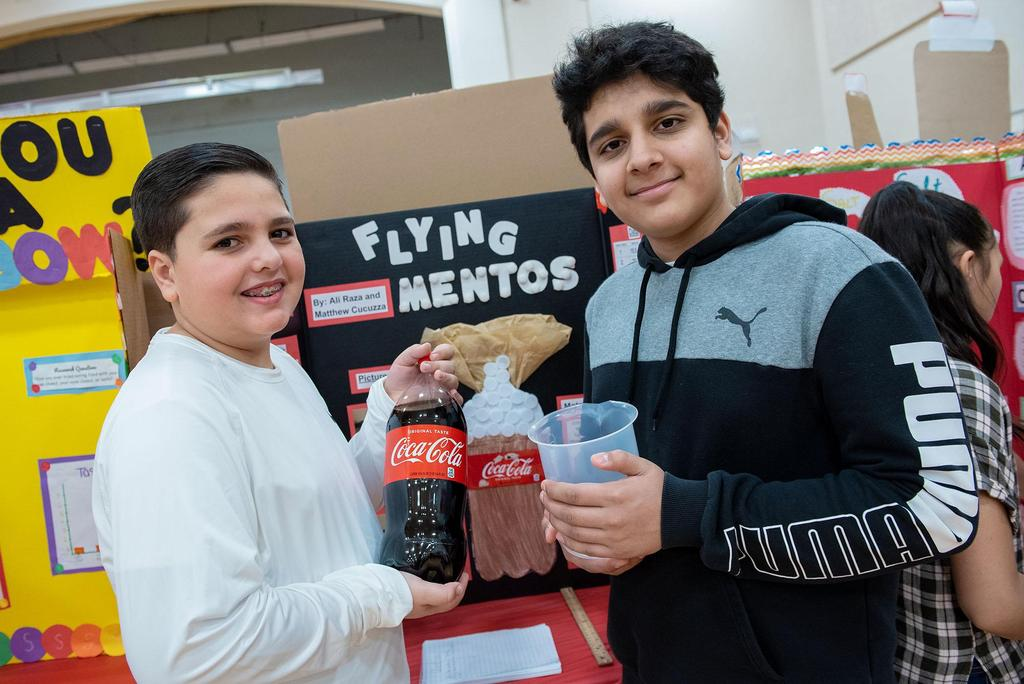 Two students hold up a two-liter container of soda and a large beaker