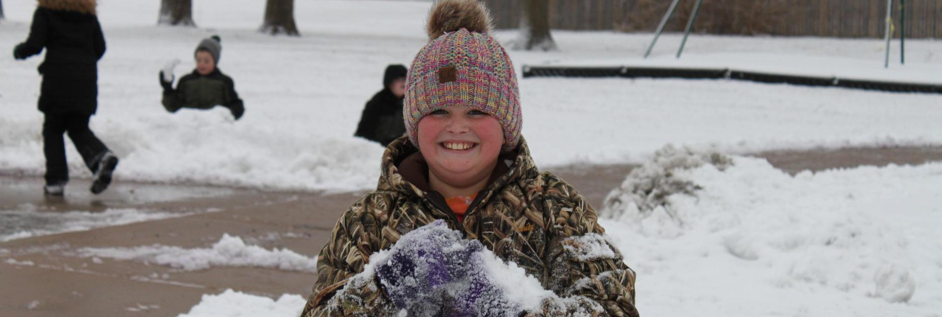 Happy student playing in the snow