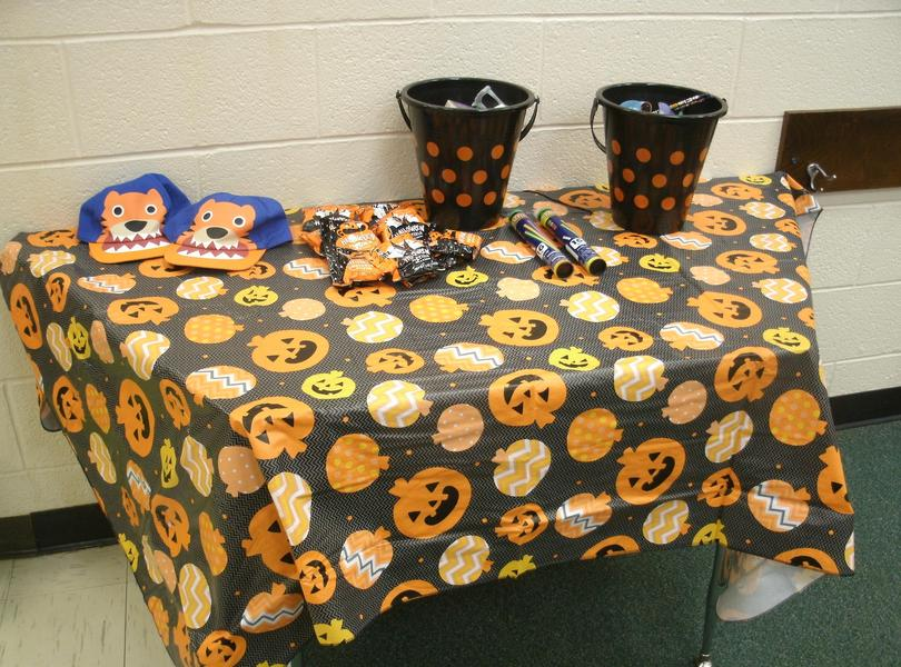 Table decorated with pumpkin and jack-o-lantern tablecloth with buckets of prizes.