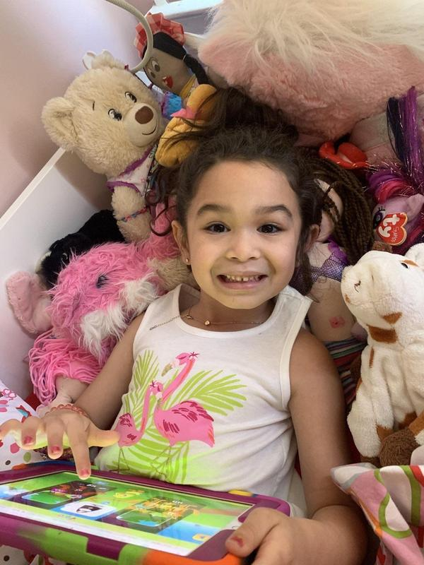 Little girl wearing a flamingo tshirt surrounded by her stuffed animals using her ipad