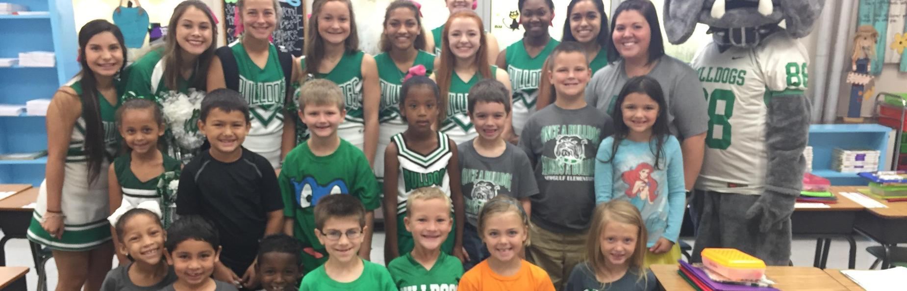 children with high school cheerleaders and mascot
