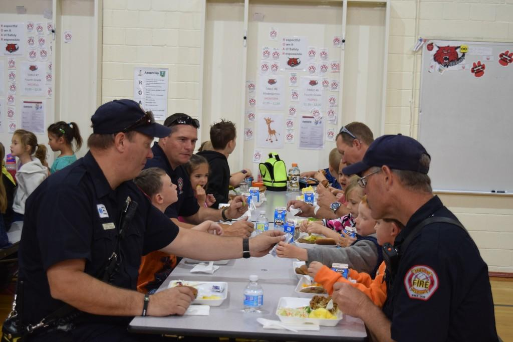 Firemen eating lunch with kids