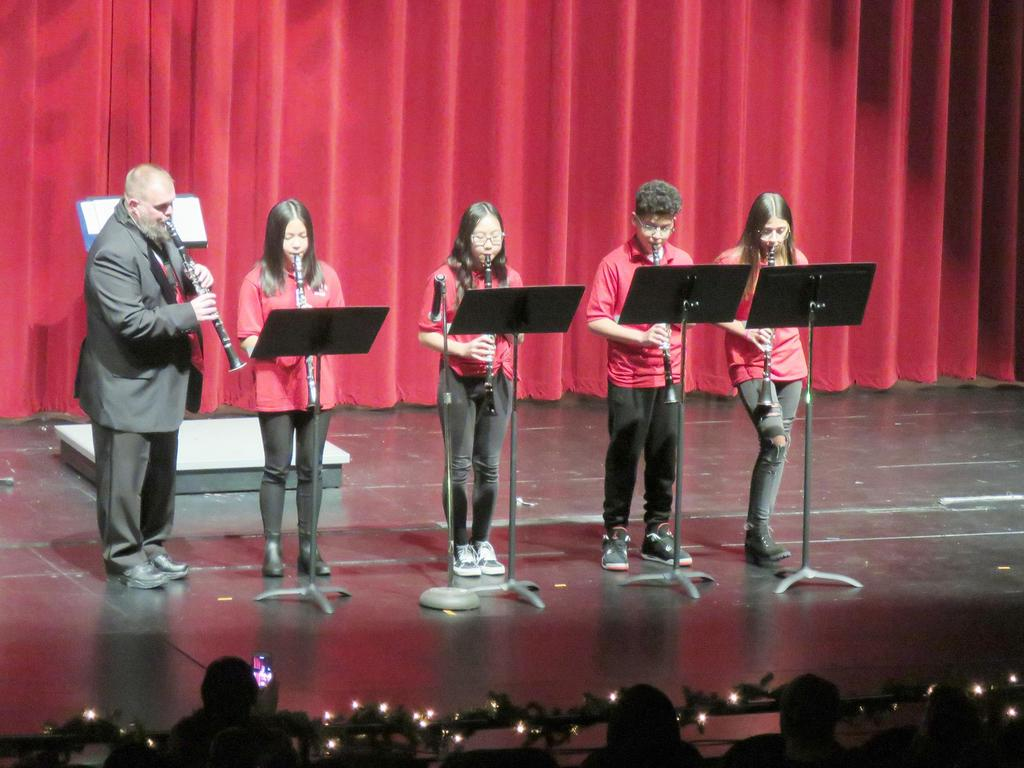 Four students and a teacher play clarinets