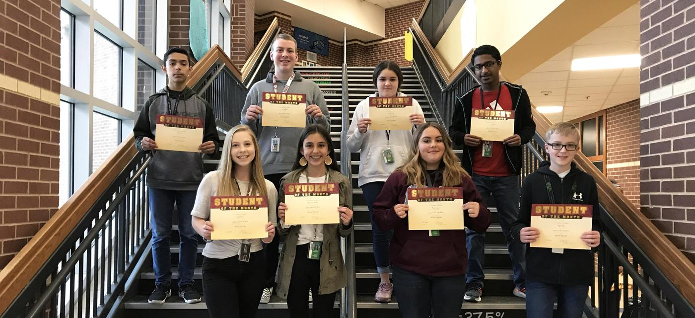 group of 8 students pose on steps with student of the month certificates