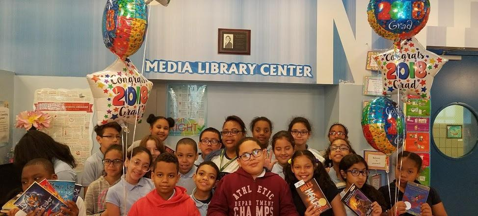 ps 192 library with a group of smiling students