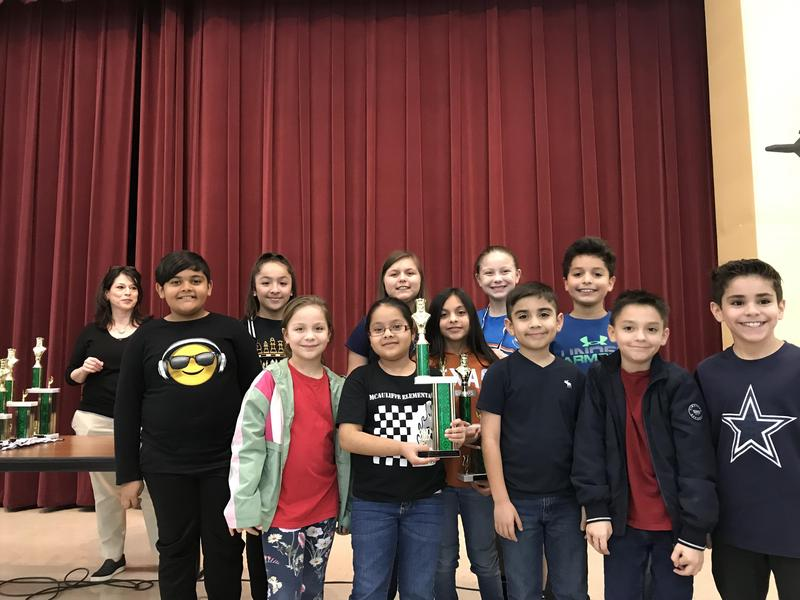 Group of chess students posing with trophy.