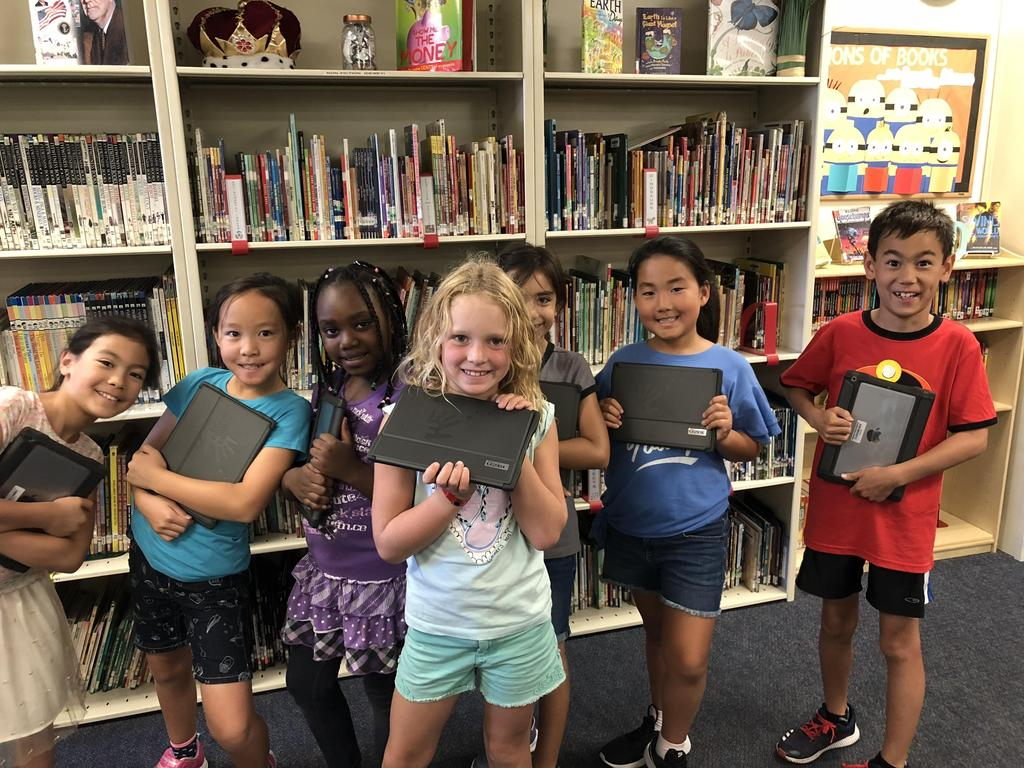 Boys and girls in the media center with their ipads.