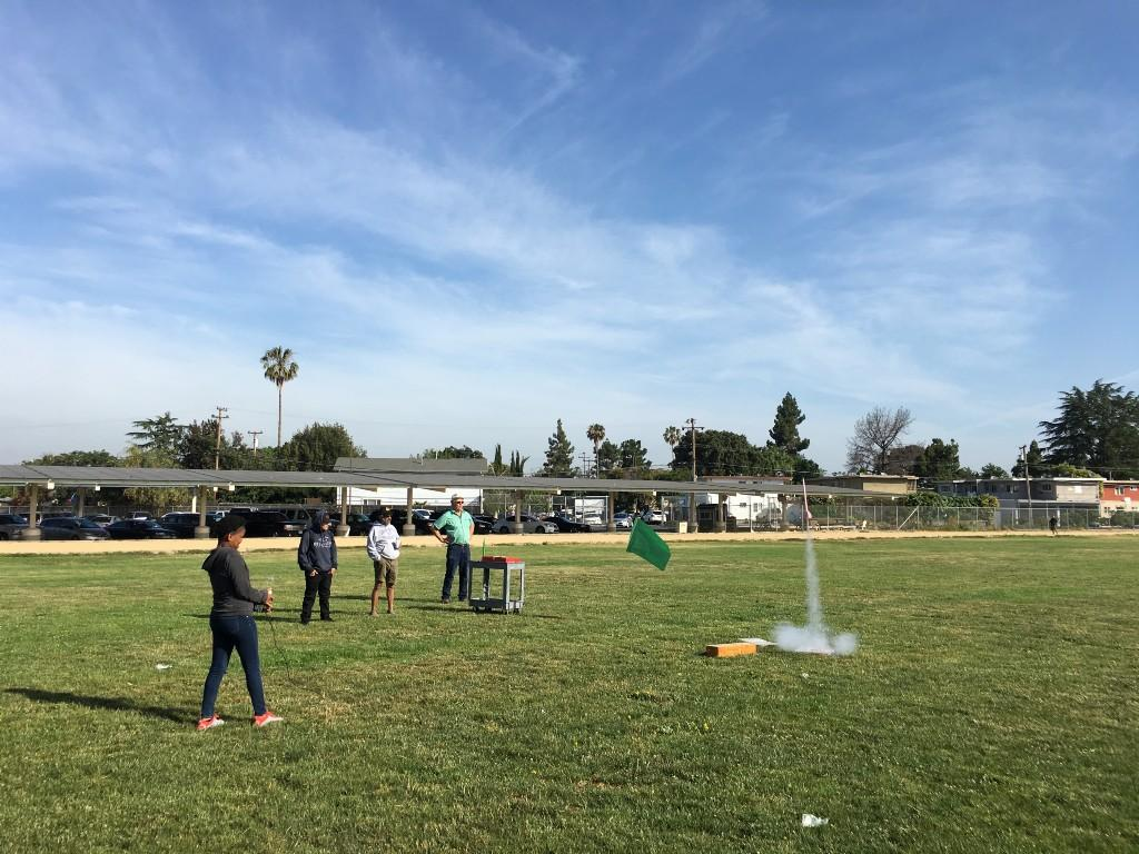 a student pushing a button on a wire that has her rocket begin to launch a few feet off the ground with teachers and a large field in the background