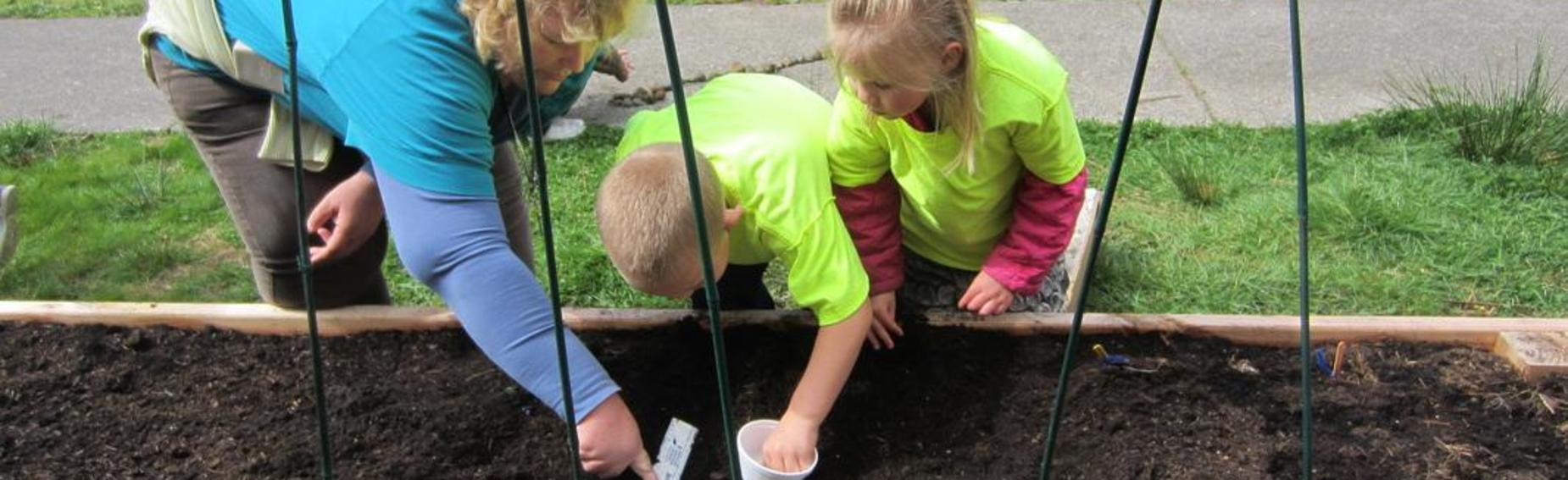 two children and an adult planting seeds in a raised garden bed.