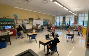 Socially distanced classroom of 1st graders raising their hands