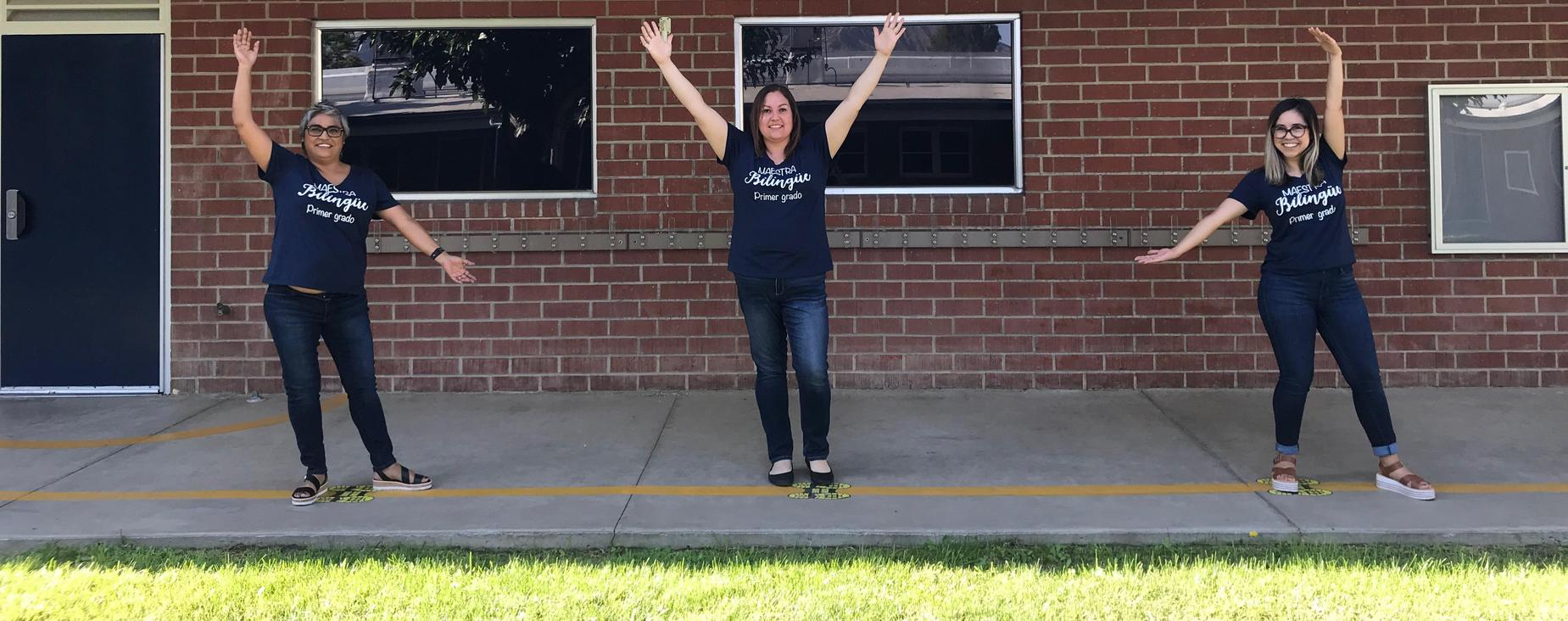 3 teachers standing with arms up