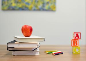 Stack of Textbooks with an apple on top. Wooden letter blocks