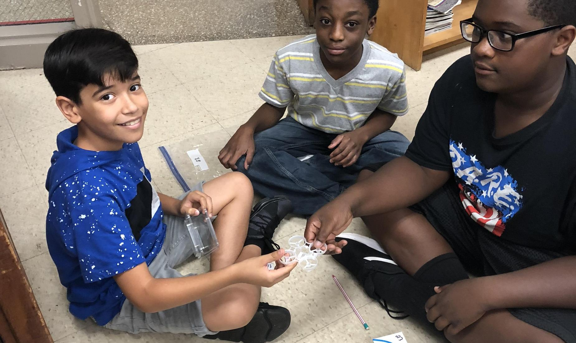 Three 6th grade students working together to build a drone in their computer class
