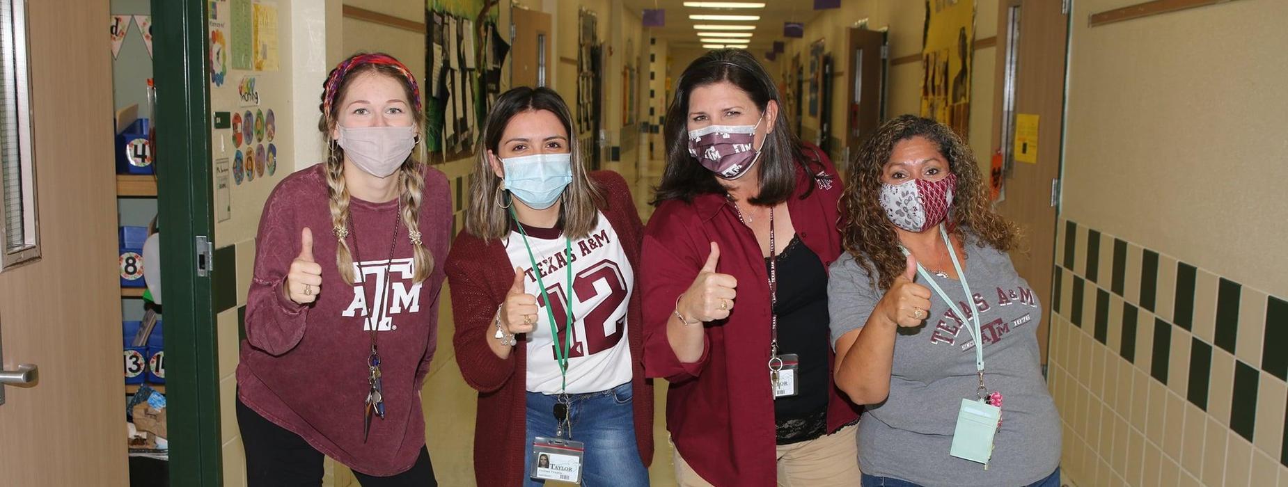 staff show college spirit wearing Texas A&M shirts