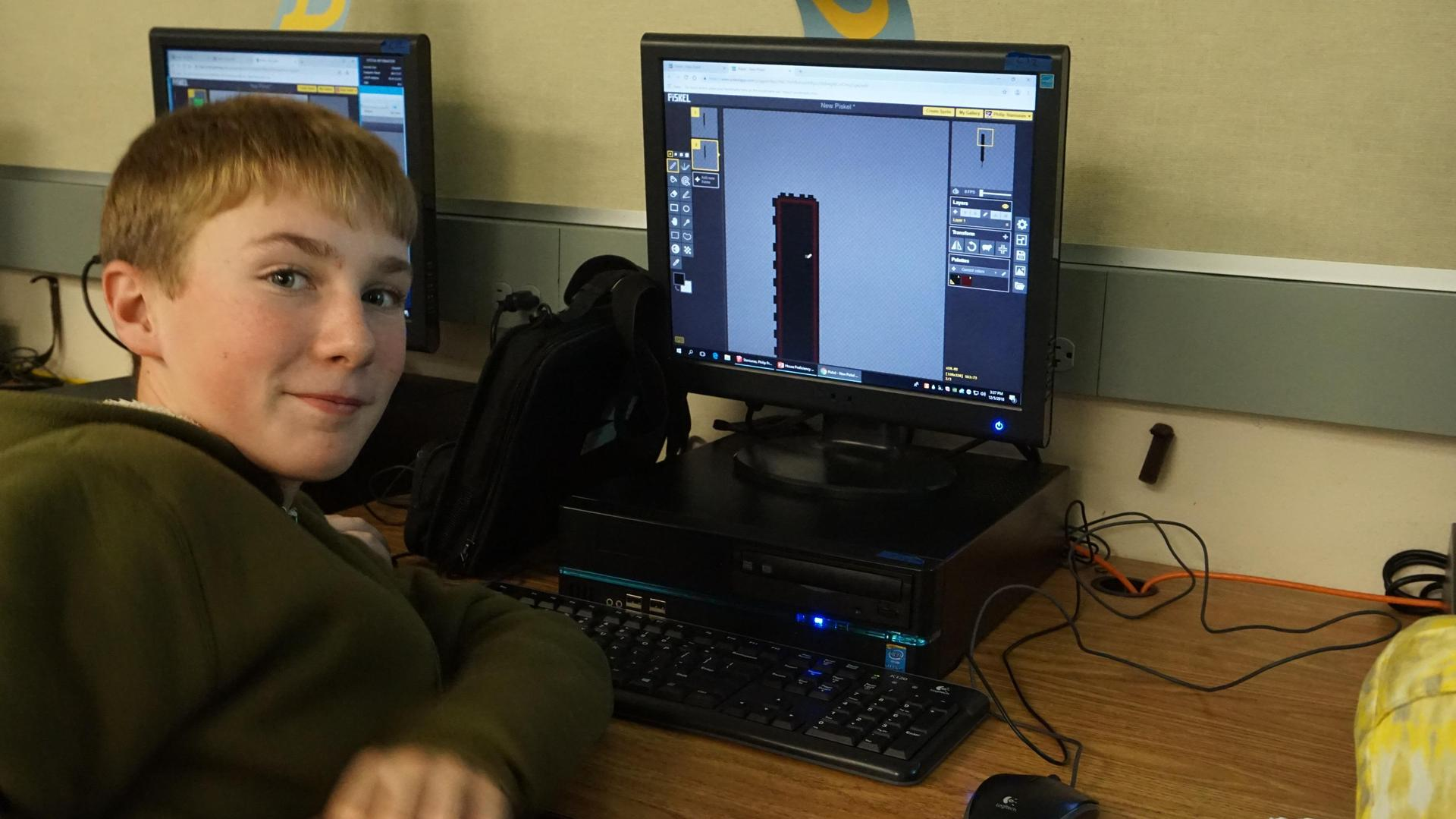 Male student showing his creation on the computer screen